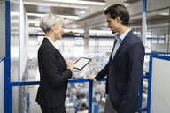 Businessman and senior businesswoman with tablet talking in a factory - DIGF05680