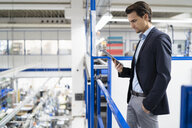 Businessman using tablet in a factory - DIGF05689
