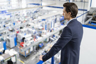 Businessman on upper floor in factory overlooking shop floor - DIGF05692