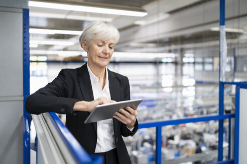 Senior businesswoman using tablet in a factory - DIGF05695