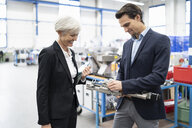 Smiling businessman and senior businesswoman examining workpiece in a factory - DIGF05701