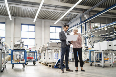Businessman and senior woman looking at plan in a factory - DIGF05722