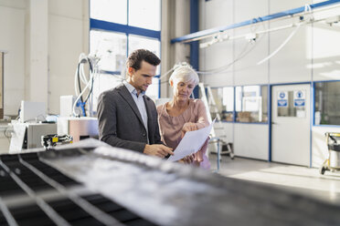 Businessman and senior woman looking at plan in a factory - DIGF05728