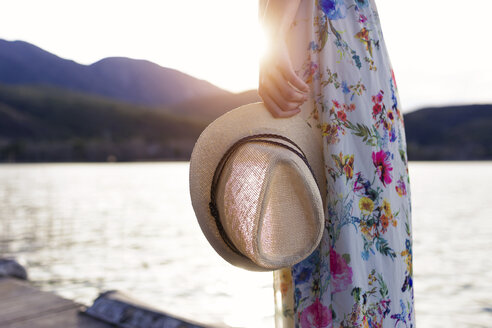 Close-up of young woman holding straw hat on wooden pier near to lake. - JSRF00108