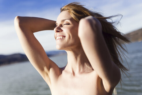 Happy young woman in front of lake enjoying sunlight - JSRF00111