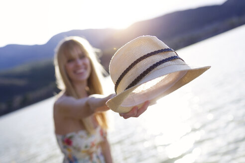 lake of Cellers, LLeida,Catalonia, Spain,Shot of pretty young woman holding straw hat on her hand and smiling at the camera on the pier near the lake. - JSRF00114