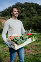 Man carrying crate with freshly harvested vegetables from his vegetable garden - GEMF02698