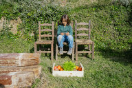 Boy sitting in garden with vegetable box, playing games on his smartphone - GEMF02713