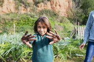 Boy showing his messy hands, full of soil - GEMF02761