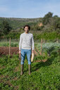 Young farmer standing in vegetable garden with straw hat and a hoe - GEMF02770