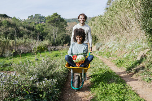 Woman sitting in wheelbarrow, holding fresh vegetables, man pushing her - GEMF02785