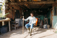 Man with a hoe sitting in a shed with a tractor - GEMF02788