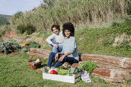 Couple sitting in their vegetable garden, having a picnic after harvesting - GEMF02791