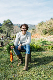 Farmer sitting on a chair, holding a bunch of carrots - GEMF02836