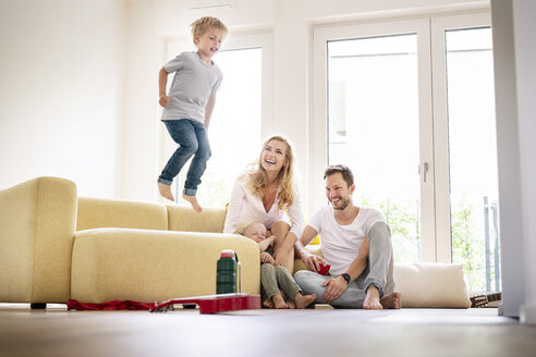 Happy family moving into their new home, boy jumping on couch - PESF01444