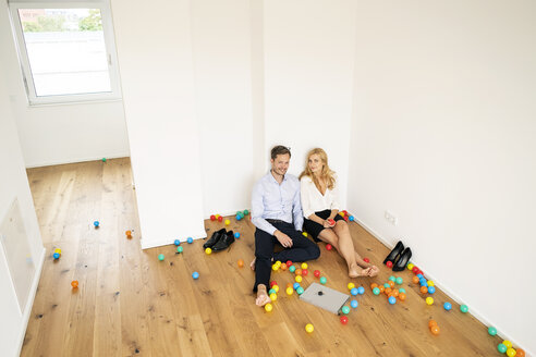 Business couple sitting on floor of their new home with colorful balls - PESF01474