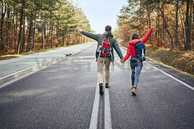 Happy couple walking in middle of an empty road in the woods - BSZF00908 - Bartek Szewczyk/Westend61