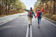 Happy couple walking in middle of an empty road in the woods - BSZF00908