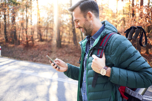 Smiling man checking smartphone on a road in the woods during backpacking trip - BSZF00911