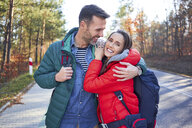Happy couple embracing on a road in the woods during backpacking trip - BSZF00914