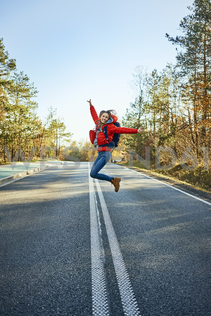 Cheerful woman jumping on an empty road during backpacking trip - BSZF00917 - Bartek Szewczyk/Westend61