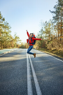 Cheerful woman jumping on an empty road during backpacking trip - BSZF00917