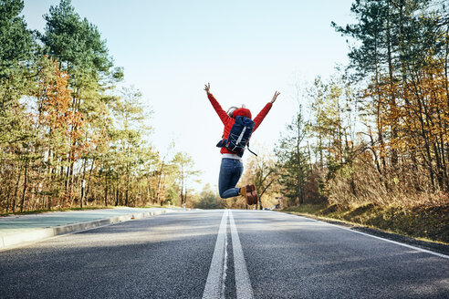 Cheerful woman jumping on an empty road during backpacking trip - BSZF00920