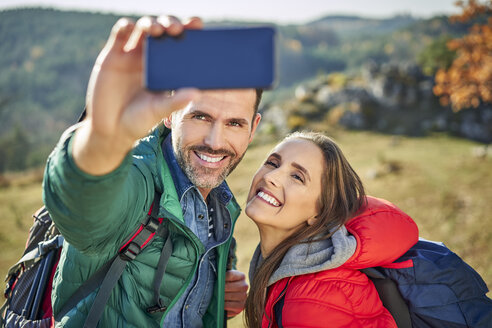 Happy couple on a hiking trip in the mountains taking a selfie - BSZF00923