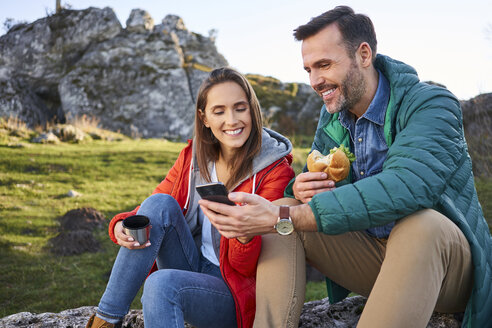 Happy couple on a hiking trip in the mountains taking a break looking at cell phone - BSZF00929