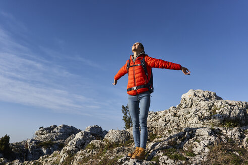Happy woman enjoying a hiking trip in the mountains - BSZF00932