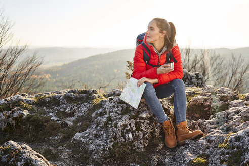Woman on a hiking trip in the mountains sitting on rock having a break - BSZF00941