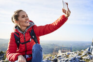 Happy woman taking a selfie on a hiking trip in the mountains - BSZF00944