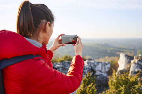 Poland, Polish Jura, Woman taking smartphone photo of beautiful view during hiking trip - BSZF00950