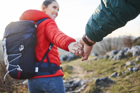 Close-up of couple holding hands on a hiking trip in the mountains - BSZF00953