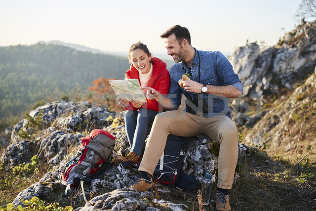 Happy couple on a hiking trip in the mountains taking a break looking at map - BSZF00959 - Bartek Szewczyk/Westend61