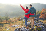 Rear view of happy couple on a hiking trip in the mountains standing on rock - BSZF00962