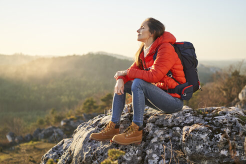 Woman on a hiking trip in the mountains resting on a rock - BSZF00965