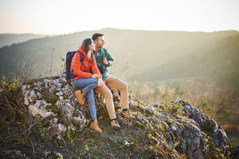 Poland, Polish Jura, Couple sitting on rocks and admiring beautiful sunset during hiking trip - BSZF00977
