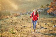 Happy woman walking on trail on a hiking trip in the mountains - BSZF00983