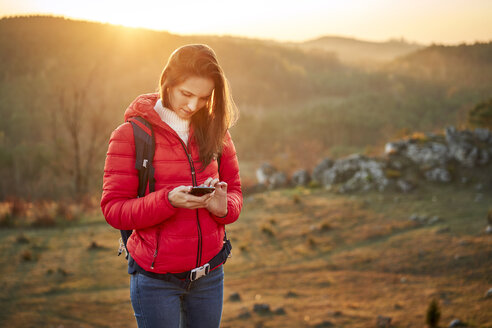 Poland, Polish Jura, Young woman checking smartphone while on hiking trip during beautiful smartphone - BSZF00986