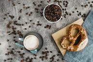 Cup of white coffee, coffee beans and pretzel on napkin and wooden board - AFVF02364