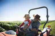 Grandfather farm and granddaughter driving tractor on sunny farm along green crops - HEROF20898