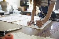 Female fashion designer tracing sewing pattern at workbench - HEROF20949