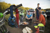Goggles hanging from motorbike handlebars near male friends drinking beer at campfire - HEROF20997