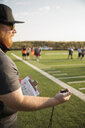 High school football coach with stopwatch timing practice on football field - HEROF21027