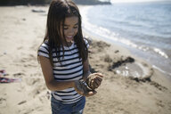 Girl playing with sand on sunny ocean beach - HEROF21036