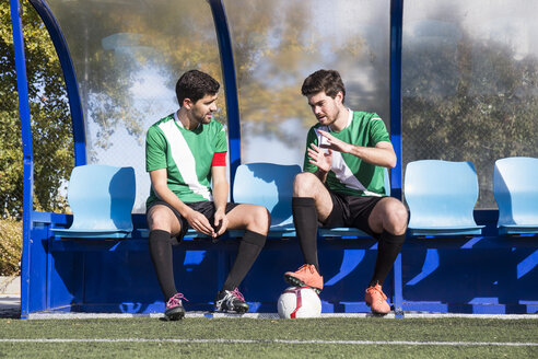 Football players sitting on bench and having nice chat before match. - ABZF02175