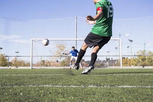 Man in sportswear kicking football with strength trying to shoot goal. - ABZF02184