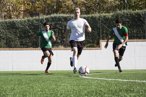 Group of players in sportswear kicking ball around soccer field playing in teams. - ABZF02187