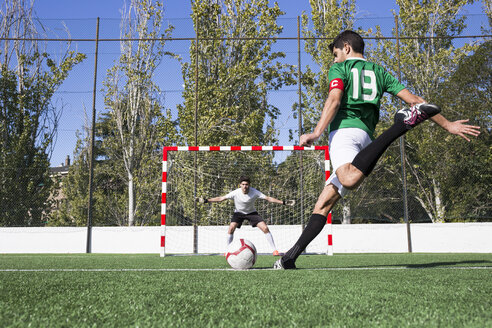 Fast football player in motion of kicking ball with strength during game on field. - ABZF02208